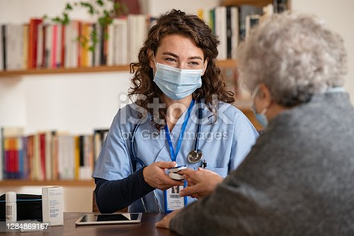 Doctor wearing surgical mask while visiting a patient at home. Senior woman sitting with doctor while doing coronavirus test and screening using oximeter. Rear view of old woman with grey hair giving finger to doctor for oximeter analysis.