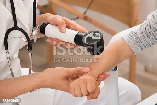 istock Doctor Examining Skin Of Child Patient 833608964
