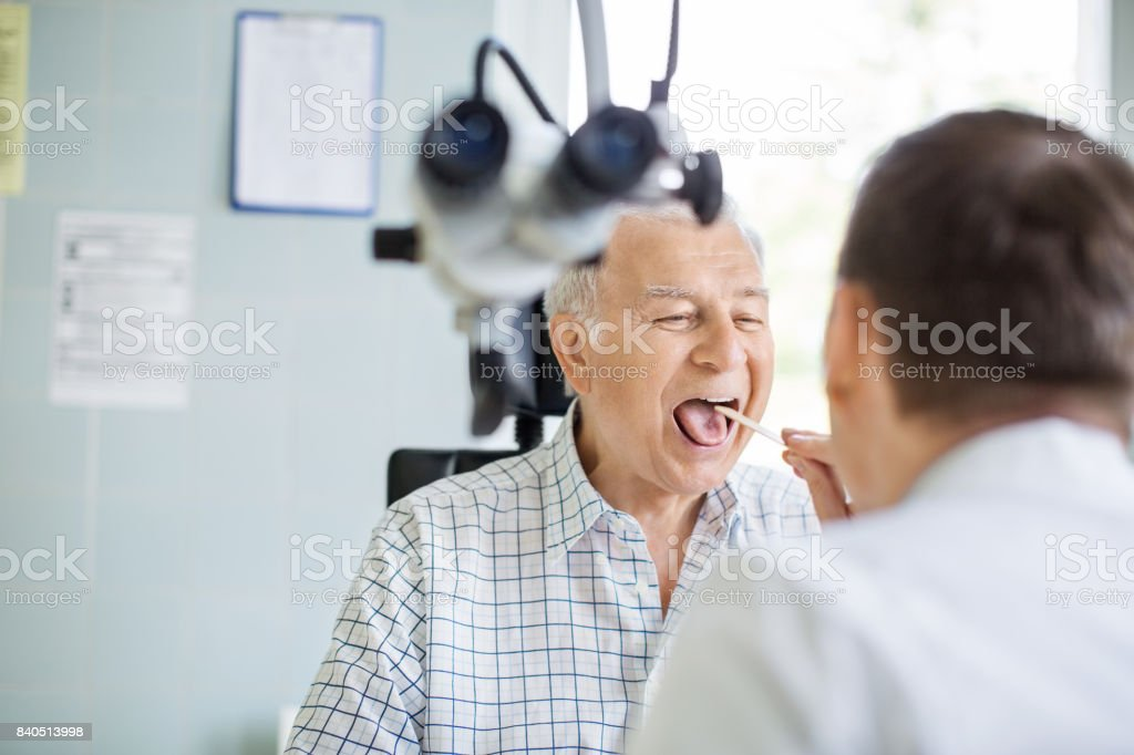 Doctor examining sore throat of senior patient stock photo