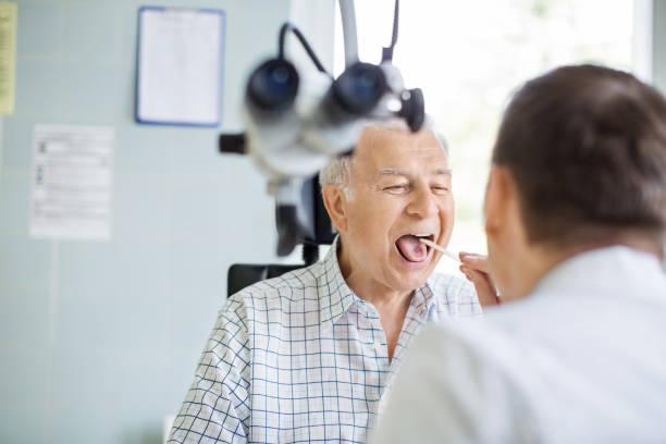 Doctor examining sore throat of senior patient stock photo