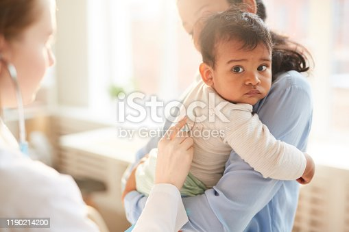 Young mother holding her little child on her hands while female doctor examining him with stethoscope at hospital