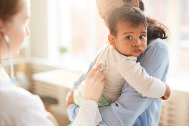 Doctor examining the child Young mother holding her little child on her hands while female doctor examining him with stethoscope at hospital pediatrician stock pictures, royalty-free photos & images