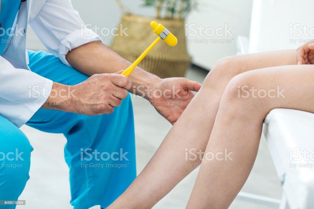 Doctor examining the knee reflex stock photo