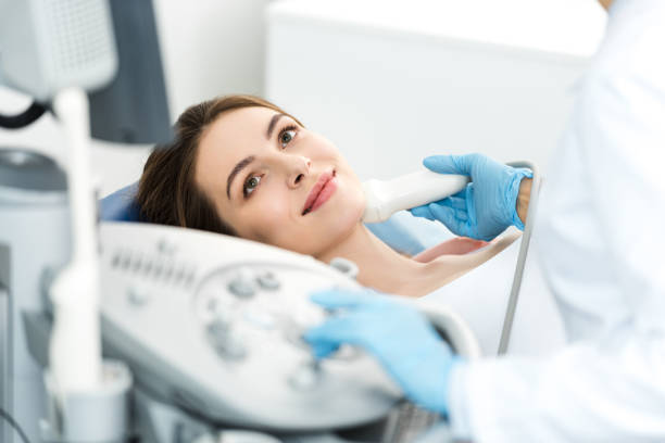doctor examining thyroid of female patient with ultrasound scan in clinic stock photo