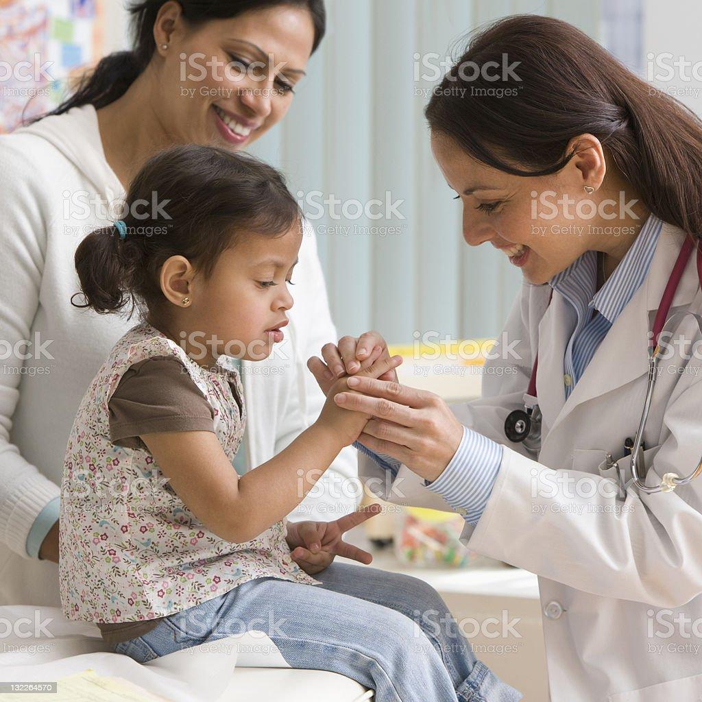 Doctor examining toddler girl's finger stock photo