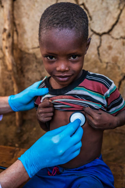 Doctor examining young African boy in small village, Kenya stock photo