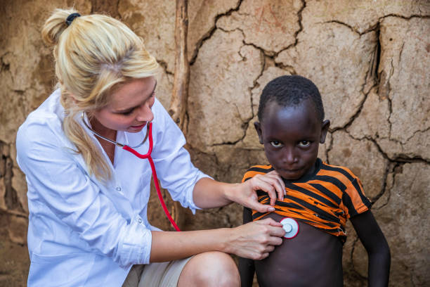 Doctor Examining Young African Boy In Small Village Kenya