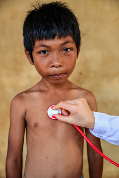 Doctor Examining Young Cambodian Boy In Small Village