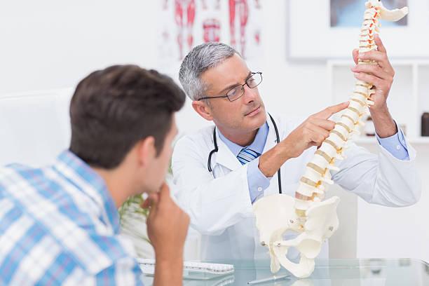 médico explicando anatômico coluna de seu paciente - ortopedia - fotografias e filmes do acervo