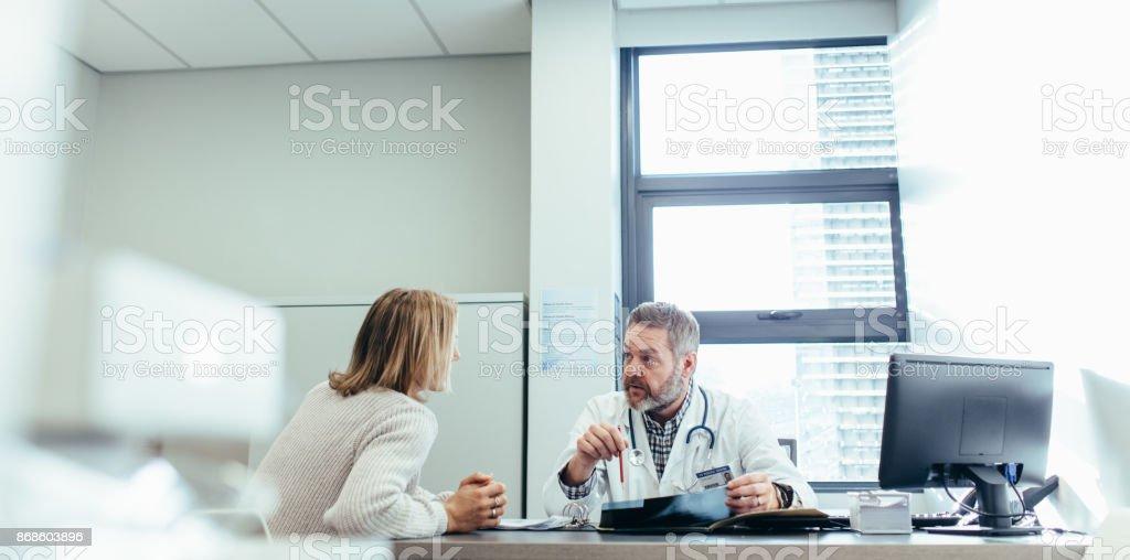Arts diagnose uit te leggen aan de vrouwelijke patiënt foto