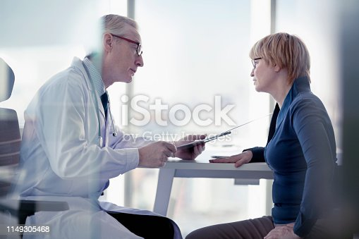 1021670950istockphoto Doctor explaining diagnosis to patient at desk in office 1149305468