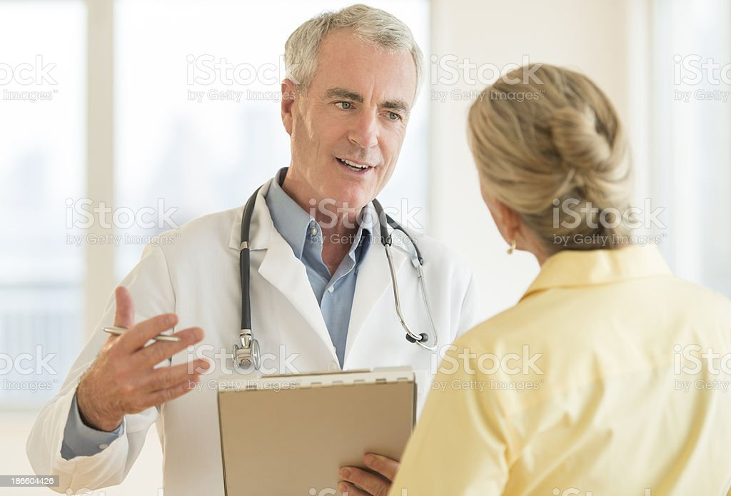 Doctor Explaining Report To Patient In Hospital stock photo