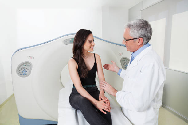 Doctor explains to the young lady in the room of head scan at hospital stock photo