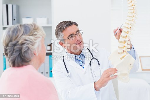 istock Doctor explaning anatomical spine to senior woman 471557494