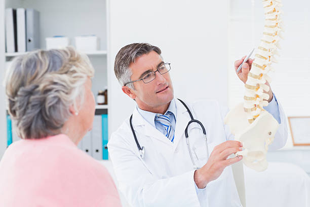 médico explaning coluna para mulher sênior anatômico - ortopedia - fotografias e filmes do acervo