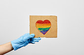 LGBTQ friendly healthcare system worker holding handmade placard with heart-shaped rainbow flag. LGBTQ doctor fighting on frontline against coronavirus