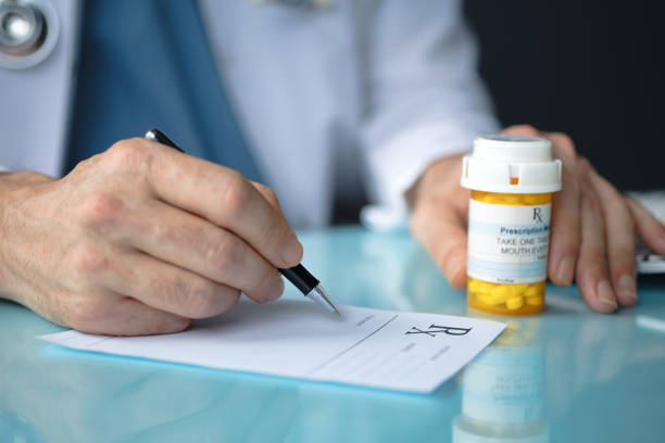 Doctor filling out a prescription Doctor filling out a prescription prescription stock pictures, royalty-free photos & images