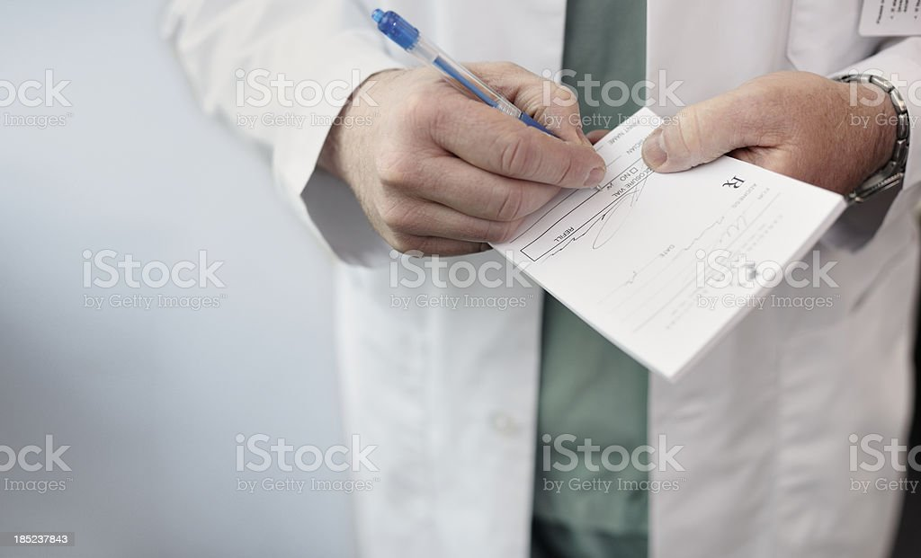Doctor filling out a prescription stock photo