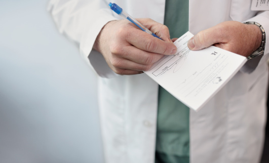 Doctor Filling Out A Prescription Stock Photo - Download Image Now