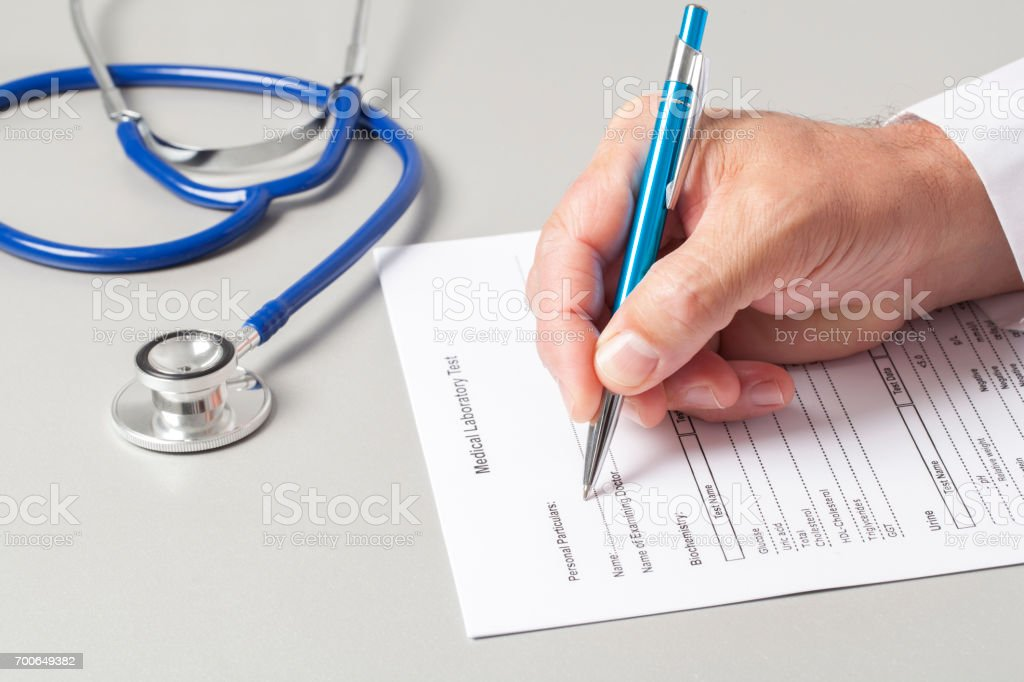 Doctor Filling Out Medical Form stock photo