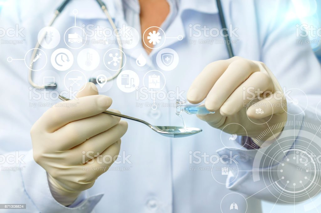 Doctor fills in a spoonful of medicine . stock photo