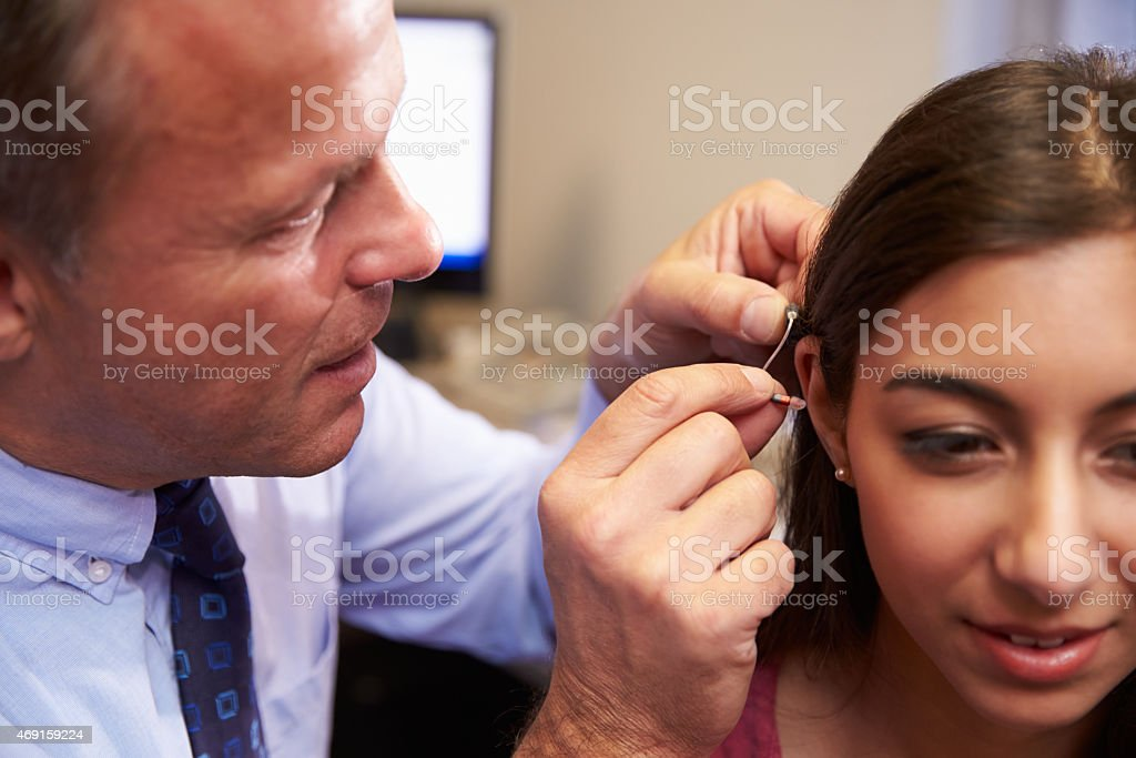 A doctor fitting a female patient with a hearing aid stock photo