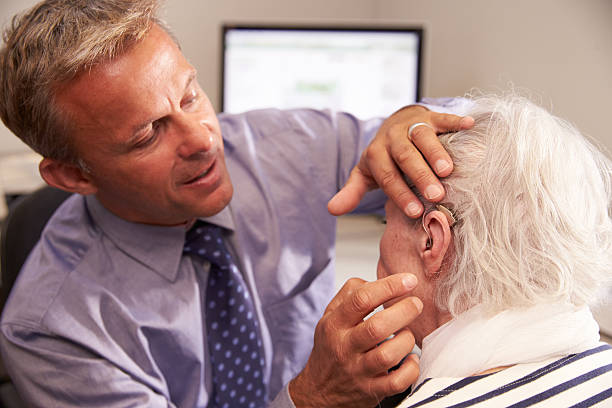 Doctor fitting a senior female patient with a hearing aid stock photo