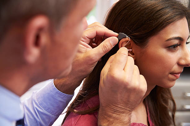 doctor fitting female patient with hearing aid - hearing loss stock pictures, royalty-free photos & images