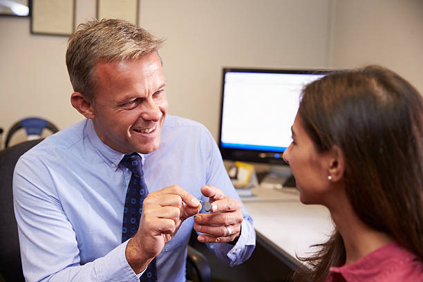 Doctor Fitting Female Patient With Hearing Aid stock photo