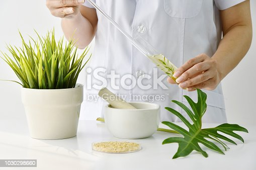 Doctor formulating new drug from organic natural plants, Pharmacist mixing extract essence substance in test tube, Alternative medicine research and development in laboratory concept.