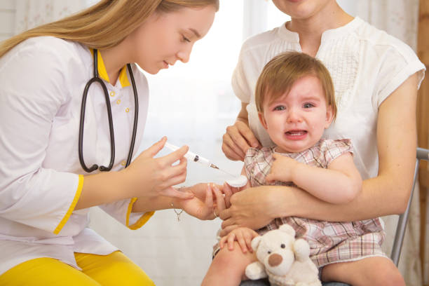 A doctor giving a crying child an injection at home stock photo