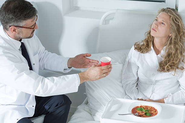 doctor giving a cup to a patient - psychiatric ward stock photos and pictures