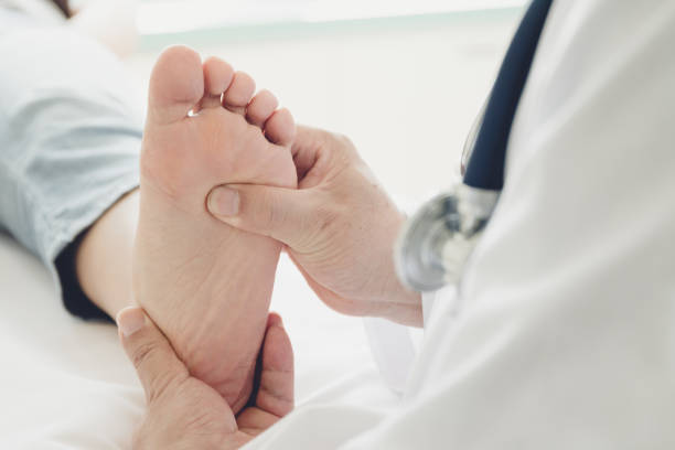 doctor giving a patient foot treatment - podiatry stock pictures, royalty-free photos & images