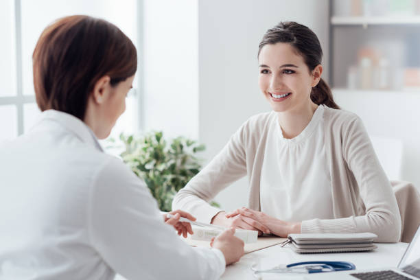 doctor giving a prescription medicine - patient talking to doctor stock photos and pictures