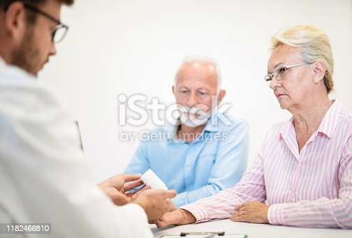 Doctor giving a prescription medicine to senior woman sitting with husband.