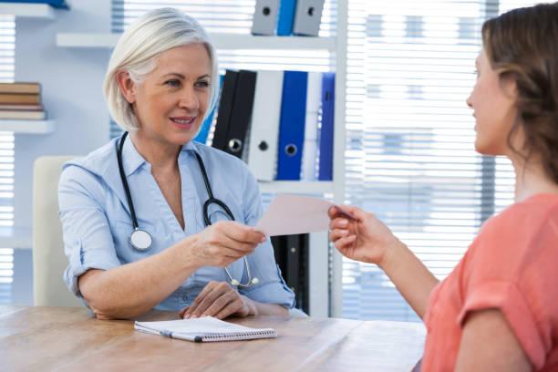 arzt ein rezept verleihen ihrer patientin in arztpraxis - südafrikanische rezepte stock-fotos und bilder