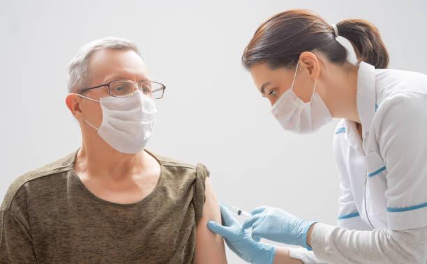 Doctor giving a senior woman a vaccination stock photo