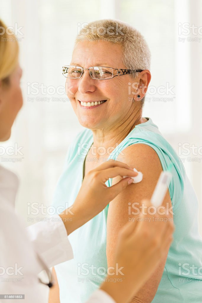 Doctor giving an injection to senior patient stock photo