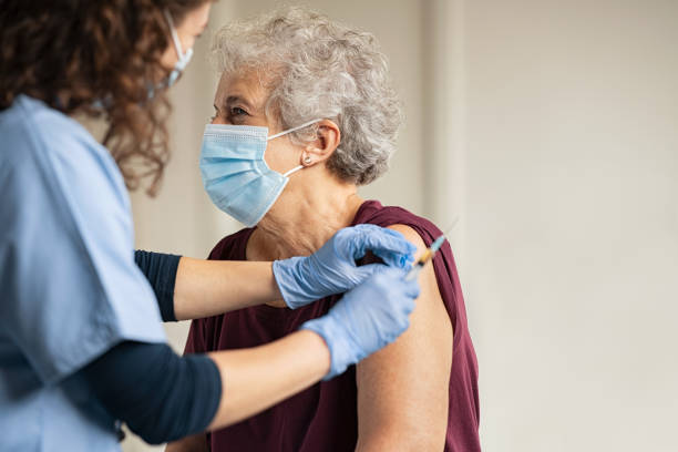 Doctor giving Covid vaccine to senior woman stock photo