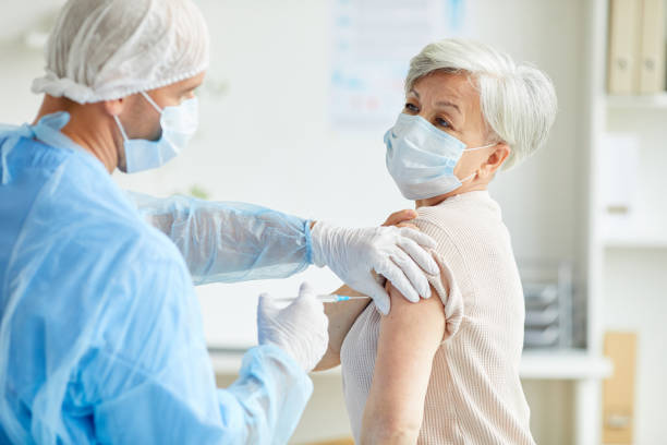 Doctor Giving Covid-19 Vaccine To Woman stock photo