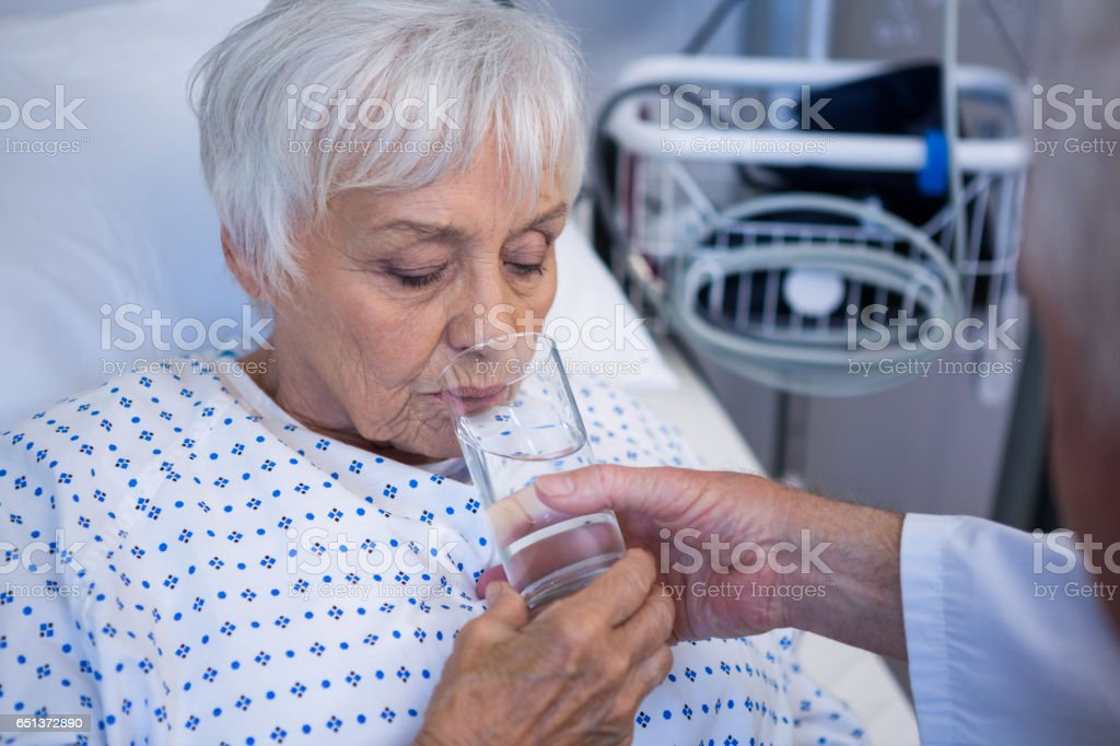 Doctor giving glass of water to senior patient stock photo