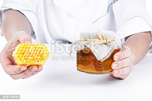 Hands of doctor holding honey jar and honey comb. Isolated over white background