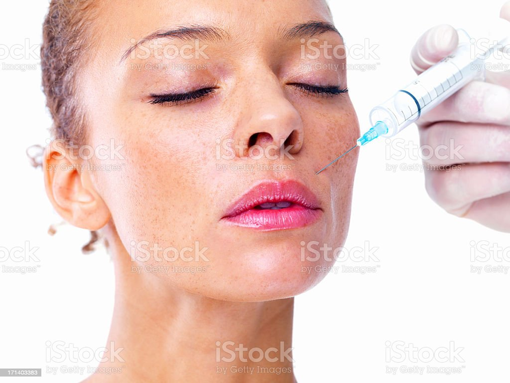 Doctor giving injection on face of a young girl stock photo
