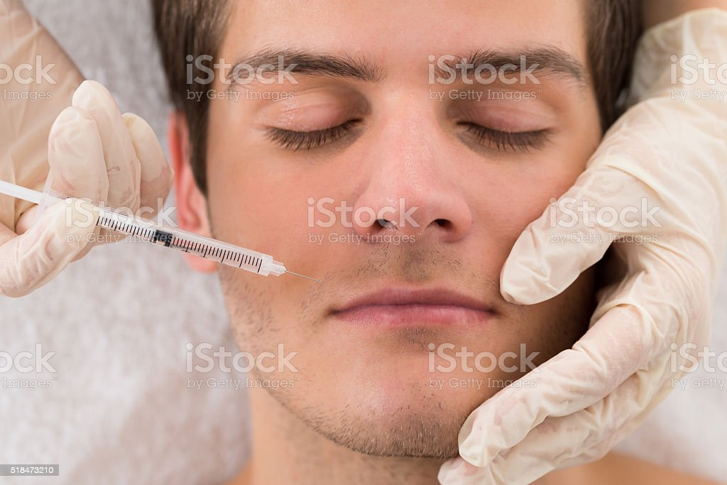 Doctor Giving Injection On Face Of Man stock photo