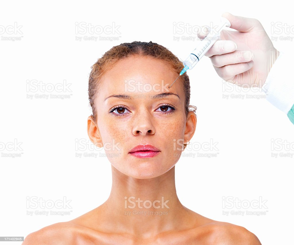 Doctor giving injection on forehead of a young girl stock photo