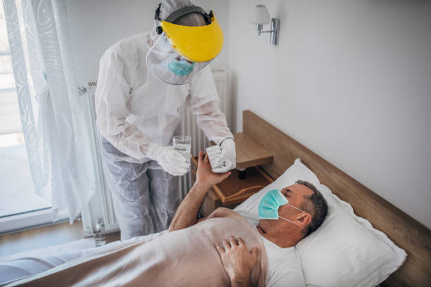 Doctor giving medicine to a senior man lying in hospital bed because of coronavirus infection stock photo