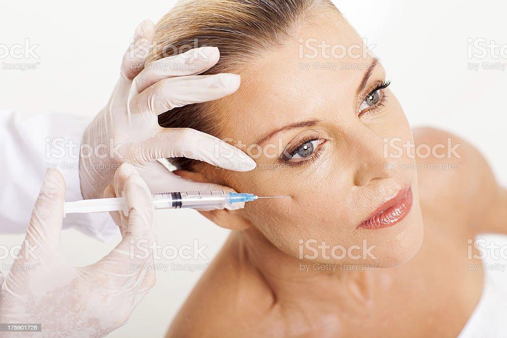 Médecin donnant milieu âge femme face injection levage - Photo