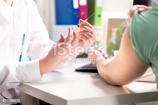 istock Doctor giving patient vaccine, flu or influenza shot or taking blood test with needle. Medicine, insulin or vaccination. 917598670