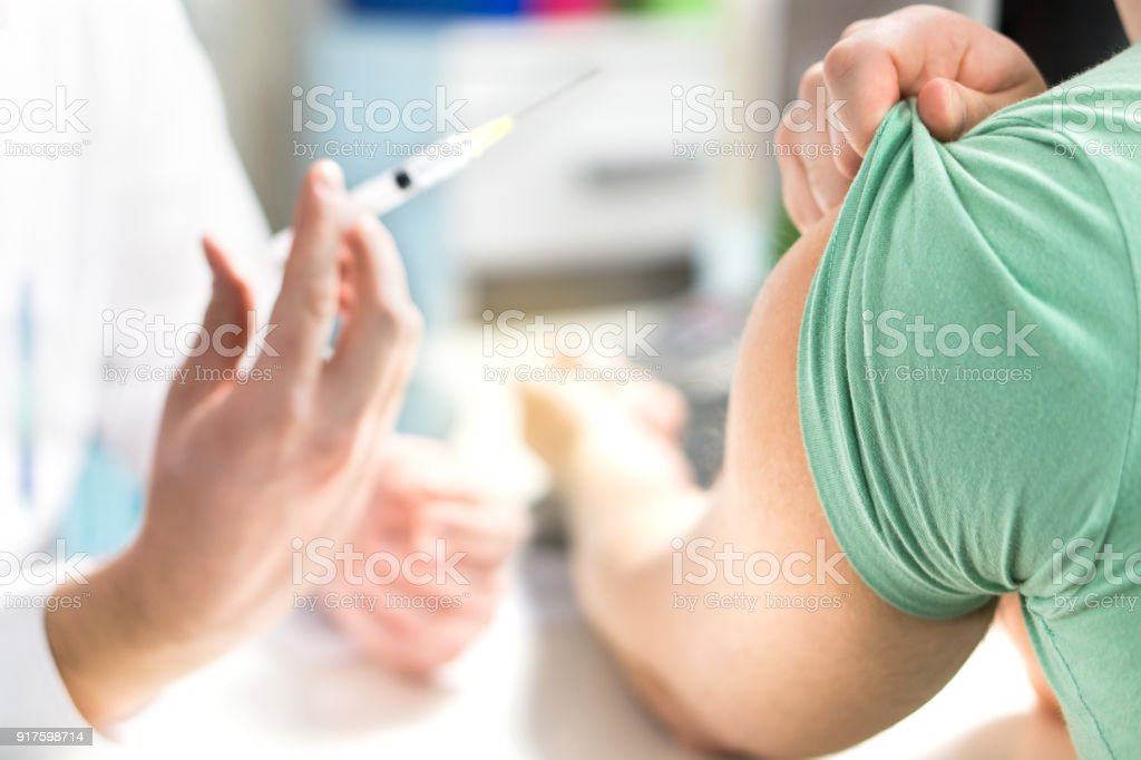 Doctor giving patient vaccine, flu or influenza shot or taking blood test with needle. Nurse with injection or syringe. stock photo