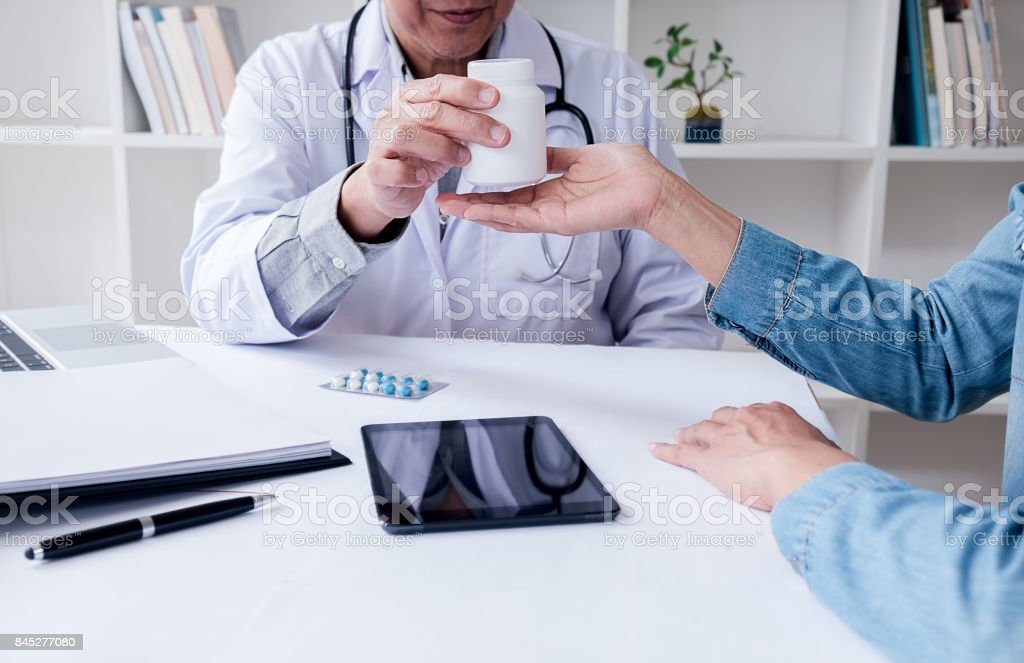 Doctor giving pills to male patient in clinic. Concept of healthcare, medical treatment and insurance. stock photo
